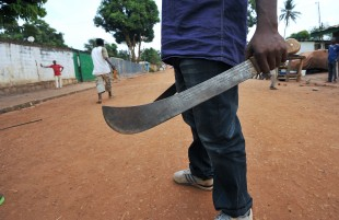 A man holds his machete as young people, who created a self-defence committee for their district Benz-vi, met before leaving for a patrol in their district, on March 12, 2014 in Bangui. UN investigators left for the Central African Republic on March 10 to launch a probe into human right violations in the conflict-ravaged country amid fears of genocide and ethnic cleansing.  AFP PHOTO/ SIA KAMBOU        (Photo credit should read SIA KAMBOU/AFP/Getty Images)