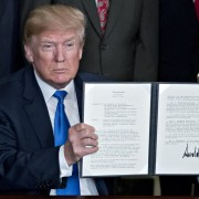 U.S. President Donald Trump holds up a signed presidential memorandum targeting China's economic aggression in the Diplomatic Room of the White House in Washington, D.C., U.S., on Thursday, March 22, 2018. Trump announced about $50 billion of tariffs against China over intellectual-property violations opening a new front in an escalating global trade skirmish that is shaking financial markets. Photographer: Andrew Harrer/Bloomberg via Getty Images