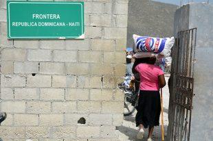 """En medio de una gran polvareda, miles de nacionales haitianos camina de un lado a otro, con sacos y cajas sobres sus cabezas, carretillas llenas de pesadas mercancías y vehículos de cargas que pasan a velocidades pocos moderadas por un camino en mal estado, se realiza un comercio informal en la frontera de Jimaní y en especial conocido como """"Mal Paso"""" o tierra de nadie.JIMANI, República Dominicana25/06/2015"""